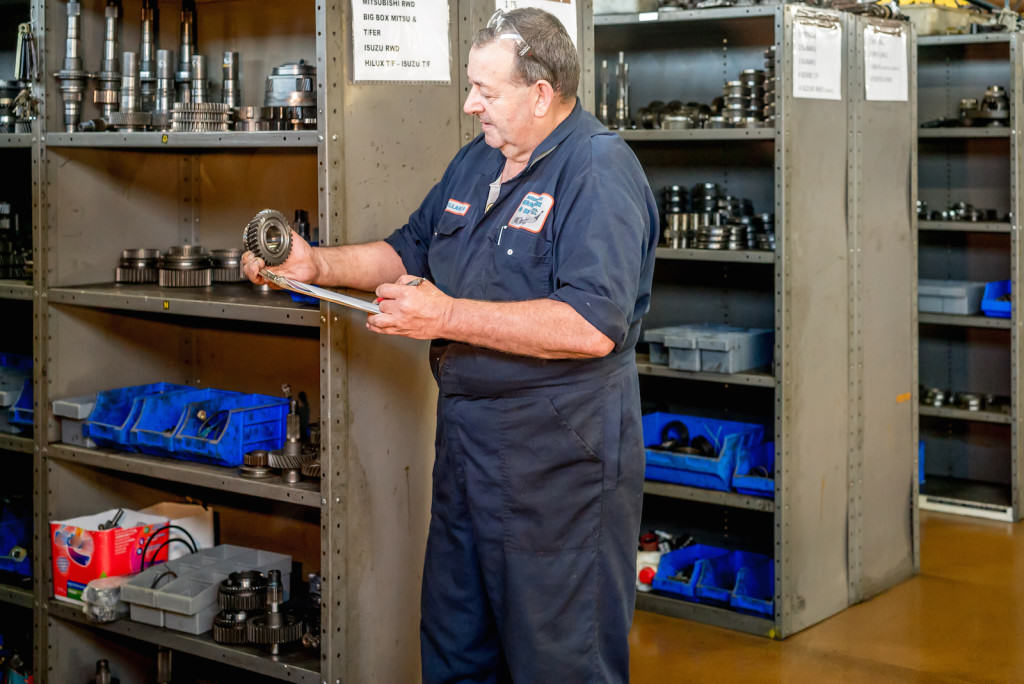 Mechanic standing in garage amidst shelves of car parts