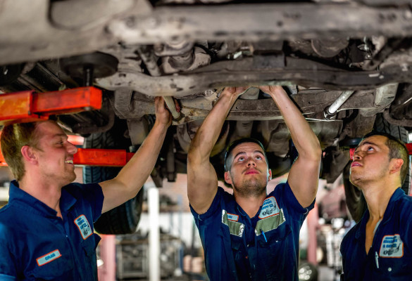 three mechanics repairing the vehicle engine from below