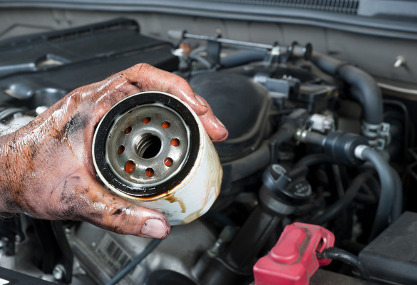 An auto mechanic shows an old, dirty oil filter just removed fro